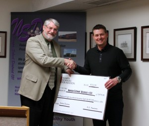President Brent Carpenter of the Nampa Schools Foundation awards Superintendent Pete Koehler a check for $9,878 to be distributed to Nampa School District Teachers.
